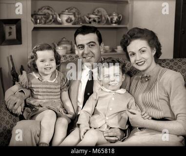 Degli anni Cinquanta la famiglia seduti sul divano insieme sorridente guardando telecamera - J3908 HAR001 HARS futuro Foto Stock