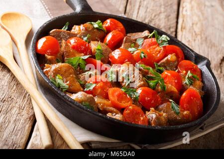 Alimenti biologici: carne in salsa piccante con pomodori verdi e close-up su una padella su una tavola orizzontale. Foto Stock