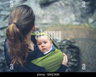 Una giovane madre è in piedi fuori in natura con il suo bambino in una imbracatura Foto Stock
