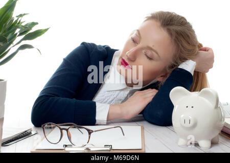 Affaticati e stanchi giovane donna che dorme sulla scrivania in ufficio, troppo lavoro Foto Stock