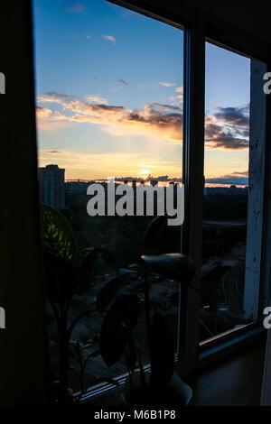 Luminose blu cielo con bianche nuvole rosa al tramonto sopra sagome scure di grandi case di città attraverso il Foto Stock