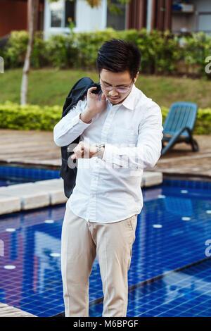 Il concetto di business - il giovane uomo d affari controllo tempo di incontro. Foto Stock