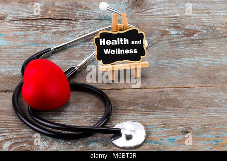 Una scheda con la parola salute e benessere e stetoscopio. Il concetto di medicina. Foto Stock
