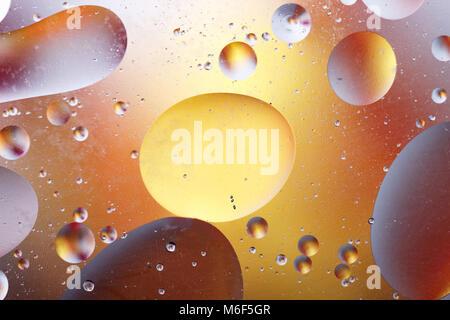 Bolle di olio in un mezzo acquoso al confine con una superficie di vetro. Abstract Screen Saver. Foto Stock