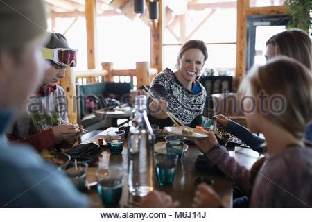 Gli sciatori in famiglia godendo il sushi al ski resort ristorante apres-ski Foto Stock