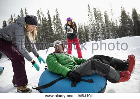 Amici a giocare, il tubo interno nella neve Foto Stock