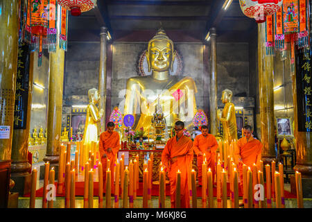Chachoengsao, Tailandia - 13 Luglio 2013: Chinse i monaci buddisti illuminazione il ceri al culto golden immagine Foto Stock