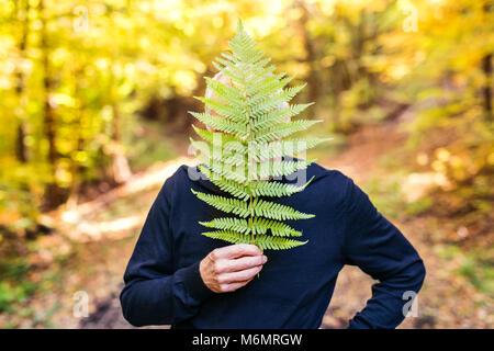 L'uomo anziano in una passeggiata nella foresta di autunno.