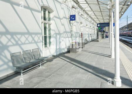 Stazione ferroviaria moderna area wainting sulla piattaforma con sedie e segno. Foto Stock