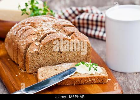 Affettato stoneground irlandese soda pane con burro e timo sul tavolo di legno Foto Stock