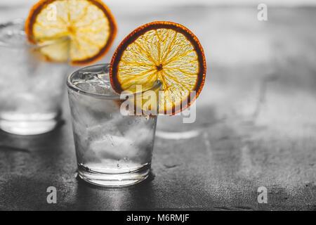 Due colpi di tequila con ghiaccio e una secca fetta di colore arancione su sfondo grigio. Foto Stock