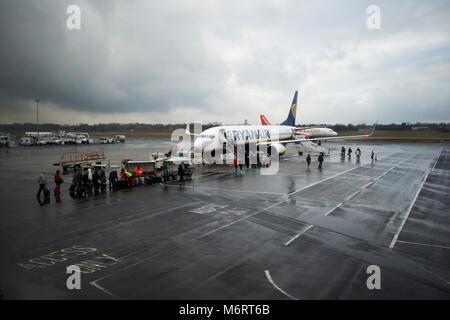 I passeggeri di caduta off bagagli e imbarco aereo Ryanair su asfalto sotto la pioggia a Belfast International Airport Foto Stock