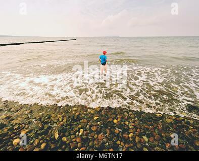 Ragazzo in blu nero abbigliamento sportivo soggiorno a freddo mare schiumoso. Capelli biondi kid in onde alla spiaggia Foto Stock