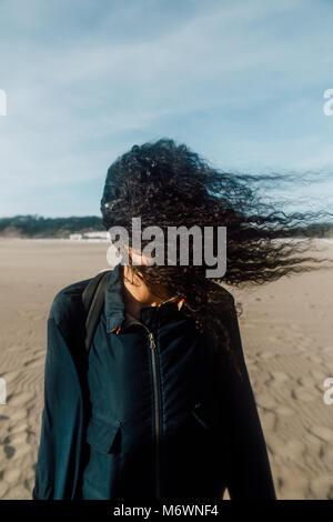 Donna sulla spiaggia con i capelli nel suo viso Foto Stock
