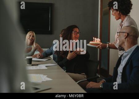 Ufficio lavoratori festeggia il compleanno di allegra collega femmina con la torta nella sala conferenze. I colleghi Foto Stock