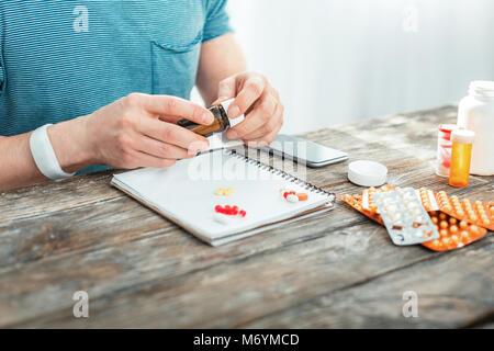 Responsabile attento uomo seduto e decomposizione di pillole. Foto Stock