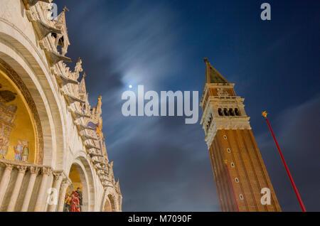 Ricerca in una luna piena durante la serata da Piazza San Marco, Venezia, Italia. Un flag pole, il campanile e la Foto Stock