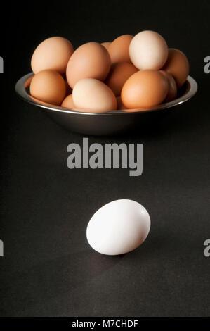 Close-up di un uovo bianco con una ciotola di uova di colore marrone Foto Stock