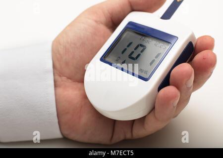 Uomo con diabete Tenendo un portable digital glucometro in sua mano di misure ha il suo proprio i livelli di zucchero Foto Stock