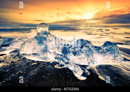 Vaganti iceberg sulla spiaggia di diamante, al tramonto, in Jokulsarlon, Islanda. Foto Stock