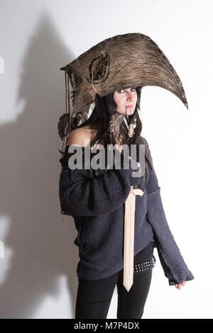 Bella ragazza vestita di strega o sciamano costume di halloween con piume nere e crow testa su sfondo bianco con Foto Stock