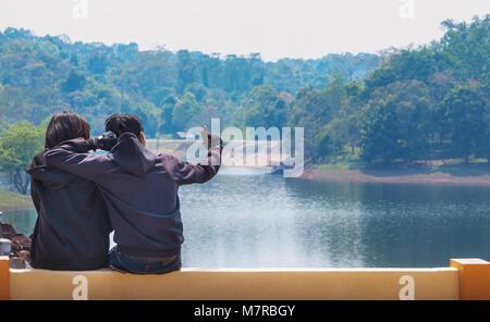 Coppia giovane rendendo selfie con smart phone. Buon viaggio giovane rendendo selfie sulle montagne e il fiume sfondo. Foto Stock