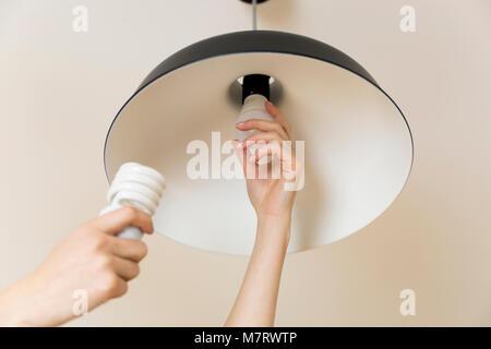 Donna sostituzione lampadina a casa. risparmio energetico lampada