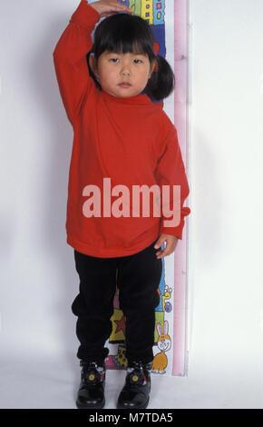 Piccola ragazza cinese in piedi nella parte anteriore del grafico di altezza Foto Stock