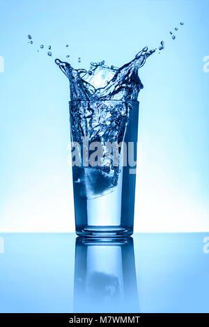 Acqua naturale Acqua Splash in un bicchiere con fondo azzurro