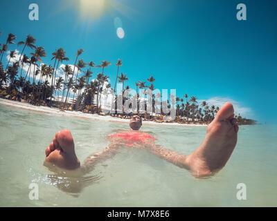 L'uomo godendo la sua vacanza estiva, acque turchesi del Mar dei Caraibi e la spiaggia di Punta Cana. Foto Stock