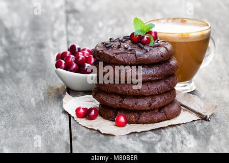 Pila di cioccolato fondente cookies con mirtillo palustre e la tazza di caffè su sfondo di legno Foto Stock
