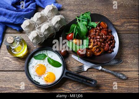 Il pan uova fritte, fagioli bianchi stufati in salsa di pomodoro e spinaci freschi. Concetto di una sana prima colazione. Foto Stock