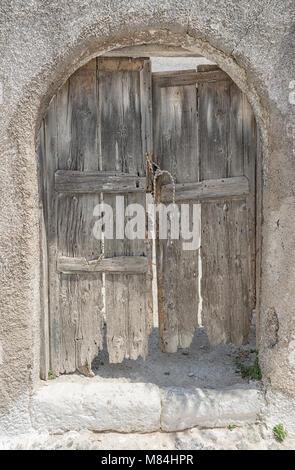 607 Emborio. Un vecchio polveroso porta i vicoli di Emborio sull'isola di Santorini, con un moderno blocco di brezza Foto Stock