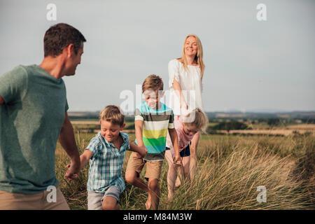 Vista frontale di una famiglia a piedi attraverso la parte superiore di alcune dune di sabbia. Foto Stock