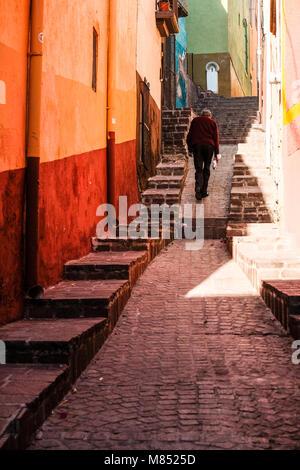 Un solitario uomo messicano a piedi fino alla acciottolato stretto vicoletto tra case colorate a Guanajuato, Messico Foto Stock