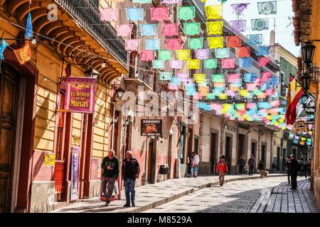 I messicani camminando sulla strada di ciottoli con sun lit banner colorati Bandiere appeso sopra Foto Stock