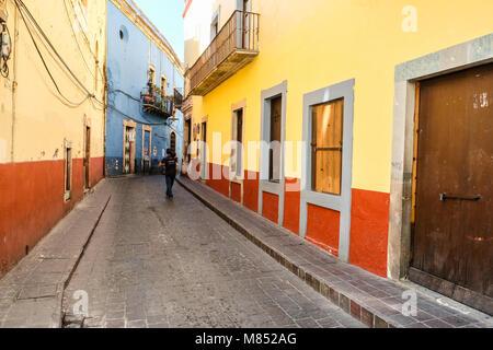 Un solitario uomo messicano a piedi fino alla stretto sentiero acciottolato in tra case colorate in Guanajuato, Foto Stock