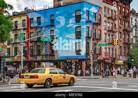 Un medaglione giallo taxi di NYC attraversa la giunzione di 1 e 9 nella parte anteriore del bean Coffee Shop in Foto Stock
