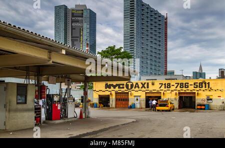 Medaglione giallo taxi Garage e stazione di gas con il Chrysler Building in distanza, Long Island City , Queens Foto Stock