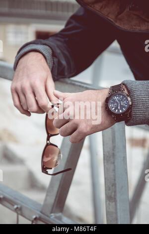 L'uomo tenendo in mano gli occhiali da sole, luxury watch visibile sulla sua mano Foto Stock