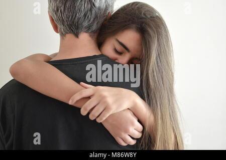 Ragazza adolescente abbracciando il suo padre Foto Stock