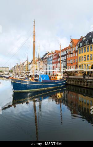 Ormeggiate barche a vela e colorata del xvii secolo città case sul canale Nyhavn, Copenhagen, Danimarca Foto Stock