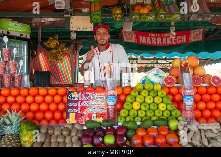 Distributore vende fresco succo pressato in una delle tante bancarelle in piazza Jemaa el Fna a Marrakech, Marocco. Foto Stock