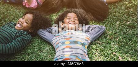 Dei bambini felici i bambini che posa in erba nel parco Foto Stock