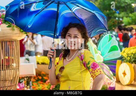 Un vietnamita donna che indossa un abito giallo e trattenimento di un ombrellone blu, Ho Chi Minh City, a Saigon, Vietnam