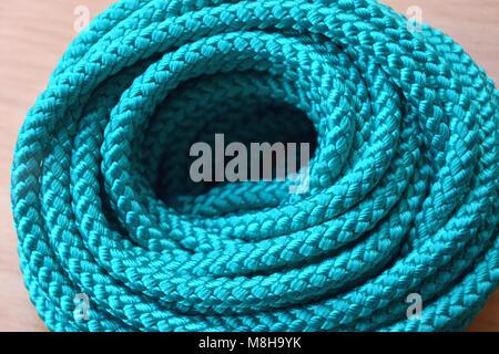Rotolo di corda in nylon in colore turchese e lo sfondo di legno Foto Stock