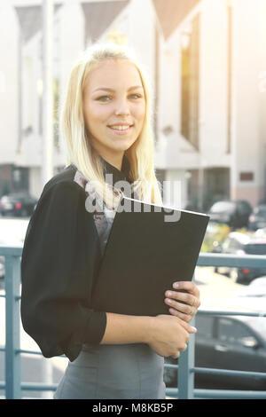 Giovane donna di affari con appunti in piedi sul balcone dell'ufficio Foto Stock