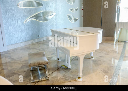 Pianoforte bianco in un interno bianco e camera di lusso. Grand piano bianco. Foto Stock