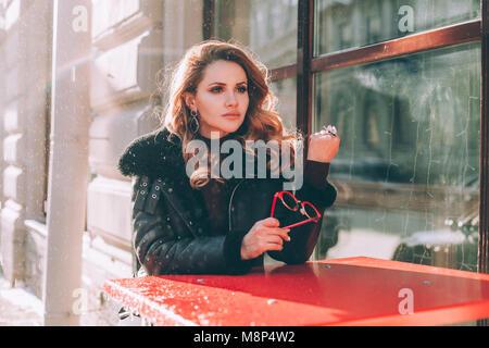 Triste donna in attesa in Street Cafe. Bambina da sola Foto Stock