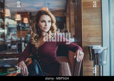 Bella giovane donna in attesa in un Cafe Foto Stock